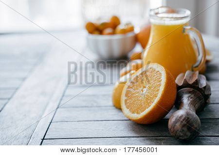 Old Wooden Table With Kumquat In A White Bowl, Oranges, Lemons And Fresh Juice Squeezer. Space For T