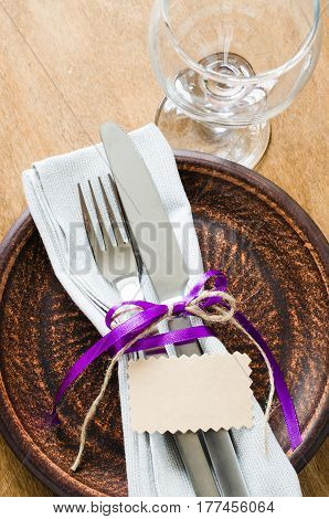 Festive Table Setting With Empty Tag. Napkin plate and cutlery on wooden table. Holidays background. Selective Focus.