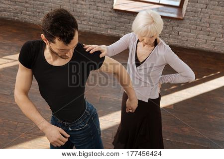 Repeat after me. Flexible confident attentive dance instructor teaching elderly woman tango while having training session and performing dance step