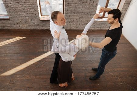 Teaching gracefulness. Careful skilled charming dance couch teaching aged pensioners tango while having training session and expressing care