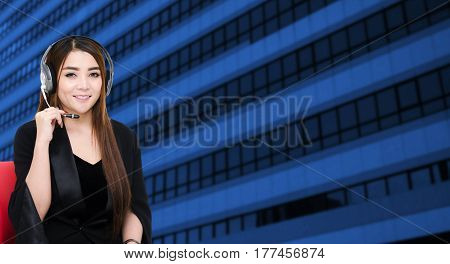 asian woman support phone operator or call center in headset sitting on red chair on building business district city background, color tone effect, customer support and service concept, copy space.