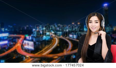 portrait of asian woman support phone operator or call center in headset sitting on red chair on blurred night city background, customer support and service concept.