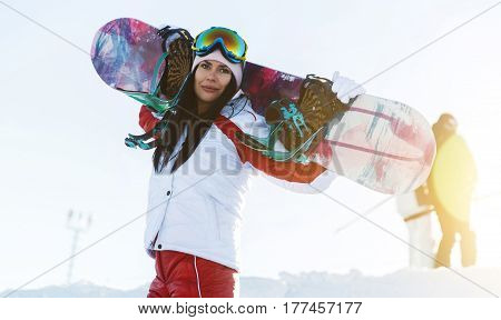 Photo of girl in ski suit with snowboard on mountain slope