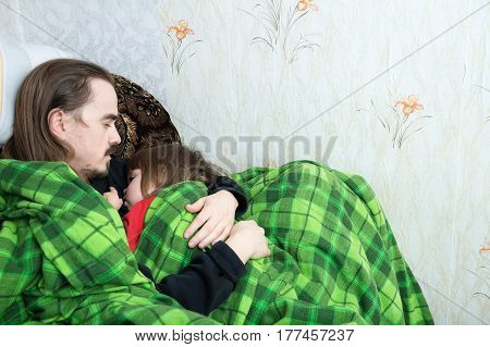 Father and child sleeping together on armchair. Family resting. Happy parenthood fatherhood. Dad and daughter wrapped in blanket sleep quite.