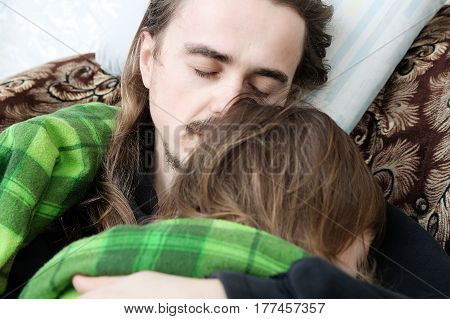 Father and child sleeping home together on armchair. Family resting. Happy parenthood fatherhood. Dad and daughter wrapped in blanket sleep quite.