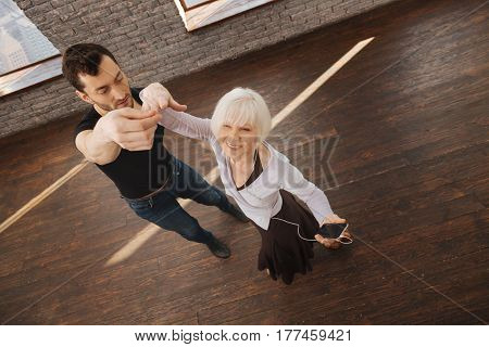 With attention to every detail. Strong careful experienced dance instructor teaching senior woman while working and demonstrating perfect posture