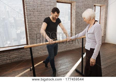 Preparing for the first dance class. Experienced athletic gifted dance couch teaching senior woman while standing next to the barre and demonstrating perfect posture