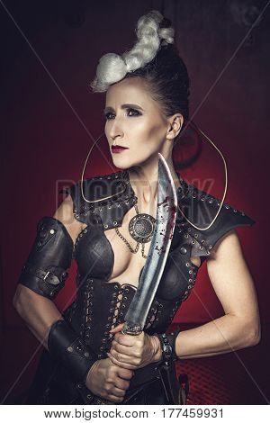 Beautiful warrior woman. Fantasy fighter. Princess or queen in leather corset ready for war. Red light and white weapon.