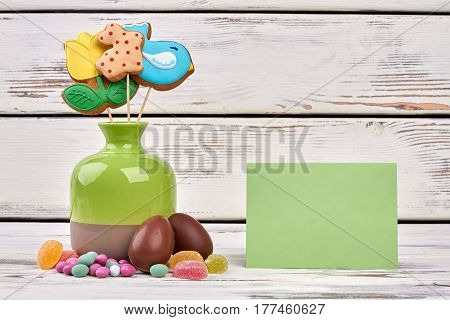 Easter sweets, blank greeting card. Jelly candies and chocolate eggs. Congratulate a sweet tooth.