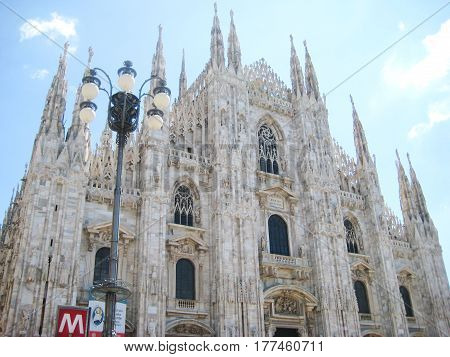 Duomo di Milano cathedral in downtown Milan, Italy. View from town square with street lantern and metro sign on sunny summer day with nobody. Travel tourism concept background.