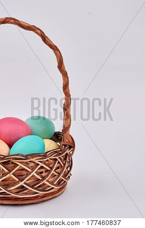 Isolated basket with colored eggs. Easter wicker basket.