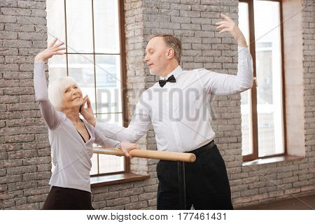 Expressing my tenderness to you. Inspired delighted aged couple performing in the art studio while dancing and using barre