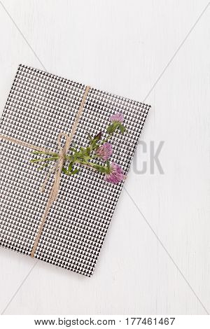 Top view on nicely wrapped gift with clover as decoration on white background. Present for birthday or any other celebration. Party. Holidays concept
