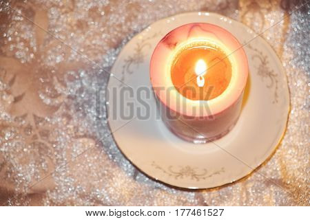 A burning white pink candle on a porcelain saucer, standing on a silver cloth