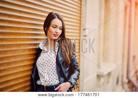 Portrait Of Stylish Young Girl Wear On Leather Jacket And Ripped Jeans Background Shutter Texture. S