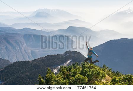 Happy celebrating winning successful man jumping with arm raised up above his head in celebration of having reached mountain top summit goal achieve during hiking travel trek in the Alps.