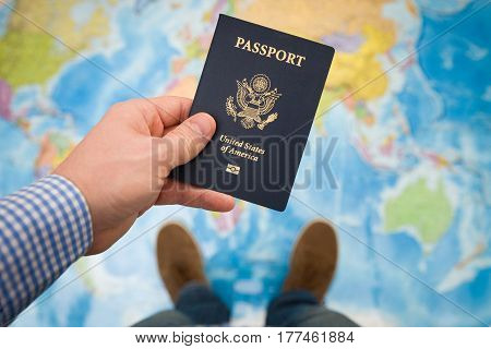 Man's hand holding US passport. Map background. Ready for traveling. Open world.