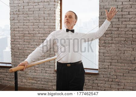 Performing classical art. Cheerful flexible confident aging man performing in the ballroom next to barre while mastering dance skills and learning new dance step