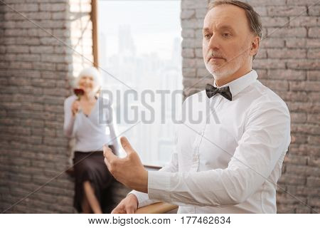 Practicing ballet together. Confident positive retired man performing in the dance studio next to barre and mastering dance skills while his wife sitting in the background