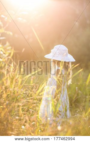 Adorable girl in a summer hat walking on a sunny flower meadow on sunset. Chinl walking in the park and enjoying summer sun. Lifestyle and summer conpcept