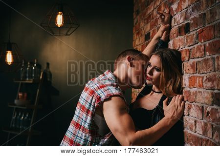 Passionate man kissing beautiful woman standing beside wall at bar