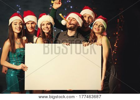 Friends with poster at Christmas party in night club