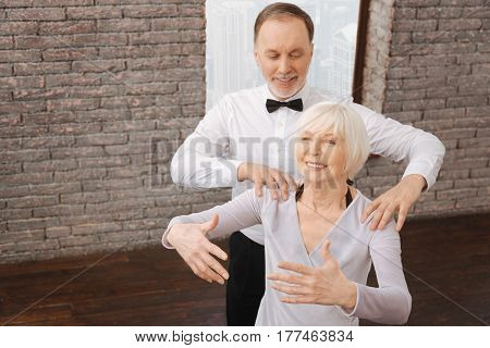 Thinking about beautiful posture. Thoughtful positive skillful senior couple warming up while taking part in the art performance and mastering ideal posture