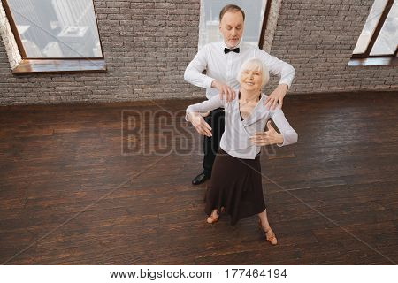 Working on every detail. Skillful flexible attentive retired couple warming up while taking part in the art performance and mastering ideal posture
