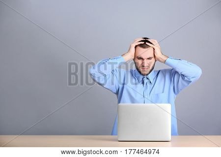 Handsome young man suffering from headache while working with laptop, on grey background
