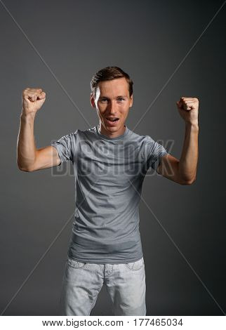 Gesture of success. Smiling man in gray t-shirt with raised hands.