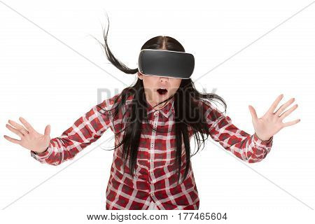 Shocked woman gesturing by hands and touching air, spending time in virtual reality. Girl in VR headset catching and playing with opened mouth, traveling in cyberspace. Flying hair and wind effect.