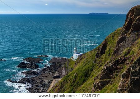 Lighthouse of the Heartland Point on the west coast of Devon. In the distance can be seen the island of Lundy. England