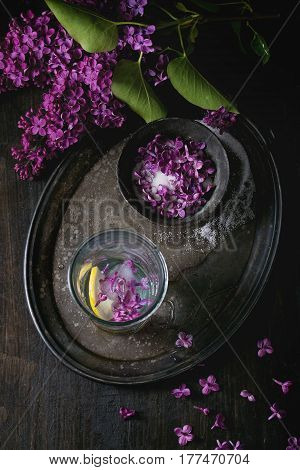 Arrangement with vintage iron bowl of lilac flowers in sugar, glass of lilac water with ice and lemon, and  lilac branch on vintage tray over black wooden background. Flat lay.