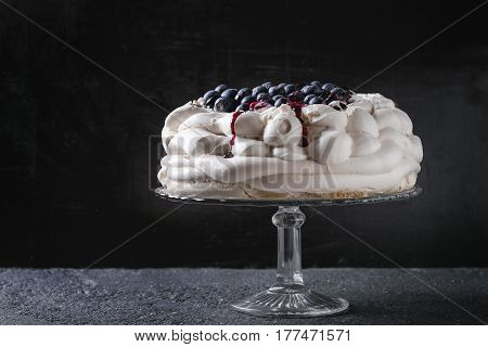 Homemade meringue cake Pavlova with whipped cream, fresh blueberries and blueberry sauce on vintage cake stand on black concrete texture background