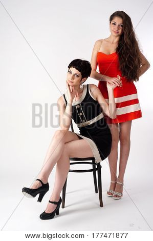 Two attractive young women with chair over white background