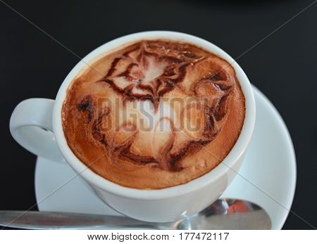 Cup of foamy cappuccino on a black table.