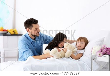 Father and sister visiting girl in hospital