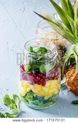 Variety of salads in mason jars. Fruit salad mango, pomegranate, greens, vegetables pasta, carrots, cauliflower, salmon. Standing with mini pineapple over blue background. Healthy food to go.