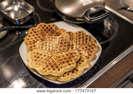 Homemade waffles are cooked in a waffle iron