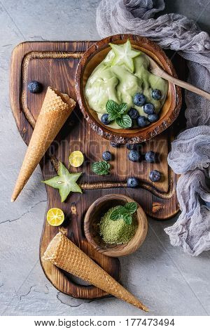 Bowl of Green tea matcha soft elastic ice cream with mint leaves, carambola, lime, blueberries and waffle cones on wooden serving board with wood spoon over gray texture background. Top view.