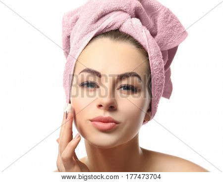 Beautiful young woman with towel applying cream onto face, on white background