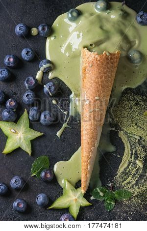 Waffle cone of melting Green tea matcha soft elastic ice cream with mint leaves, carambola, lime, blueberries over black texture background. Top view.