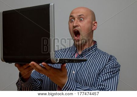 Shocked man looking at laptop computer surprised and amazed with open mouth and big eyes on a gray background