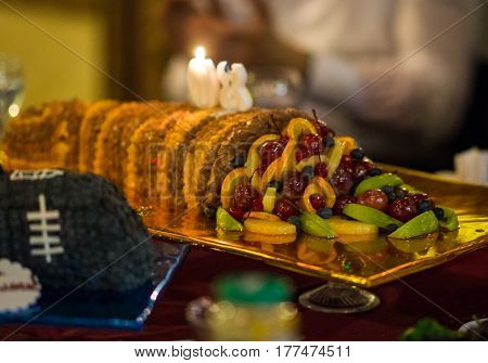 Cake With Fruit And Candles On The Festive Table