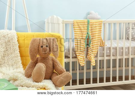 Cute bunny toy sitting on yellow sofa in baby room
