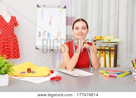 Beautiful young fashion designer working in office