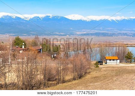 Spring landscape of the lake, trees and snow mountain peaks on the background near Bansko, Bulgaria at spring