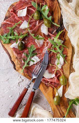 Beef carpaccio on olive wood serving board with capers, olive oil cheese and arugula, served with knife, fork, gauze textile over beige concrete texture background. Top view with space for text.