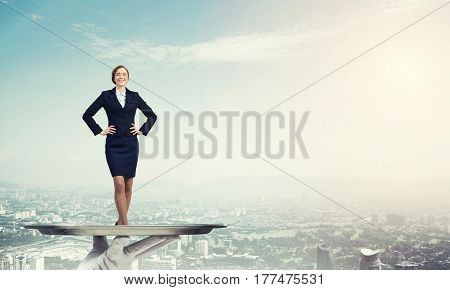 Miniature of businesswoman standing on tray held by hand