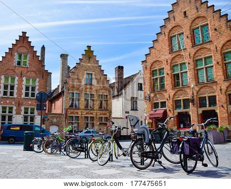 Bicycles are parked in front of historical medieval brick buildings